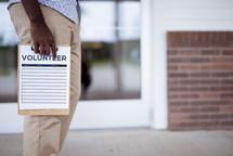 man holding a volunteer clipboard