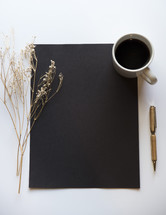blank black paper, coffee, pen, and plant sprig