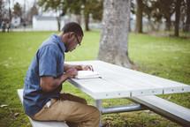 a man reading a Bible at a picnic table