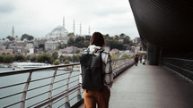 a person with a backpack walking across a bridge