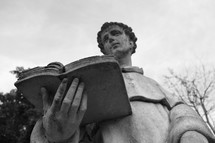 Outdoor statute of a priest reading a Bible.