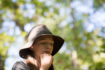 teen girl in a hat standing in a forest