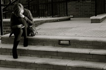 woman on steps looking at her cell phone