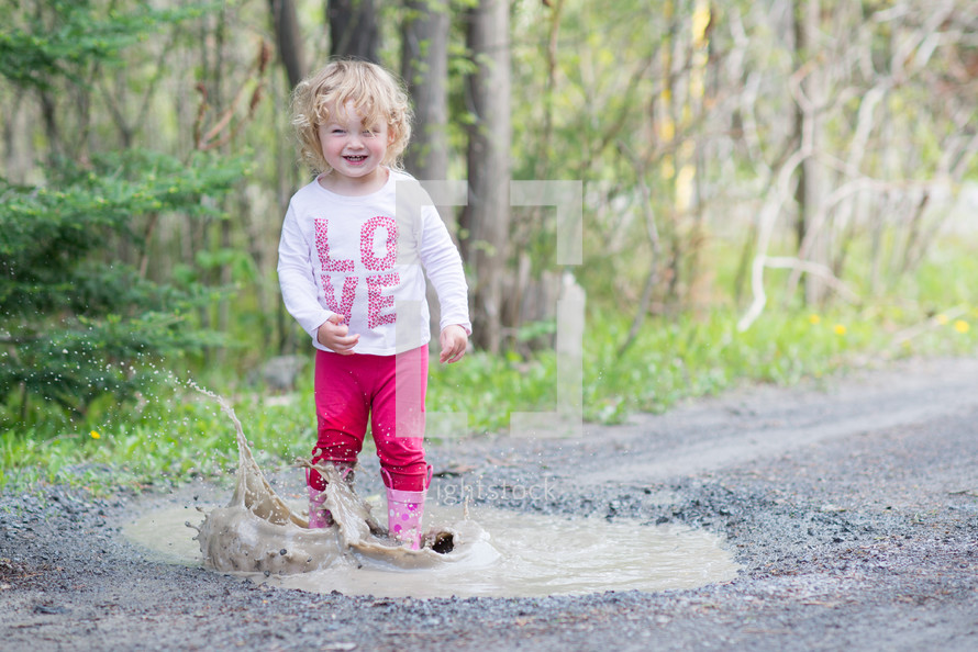toddler girl splashing in a puddle