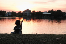 child sitting by a pond a sunset