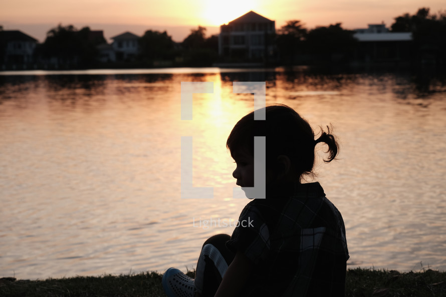 silhouette of a child by a pond at sunset