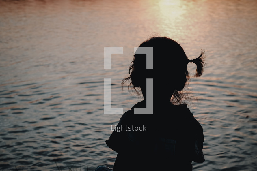 silhouette of a child sitting by a lake at sunset
