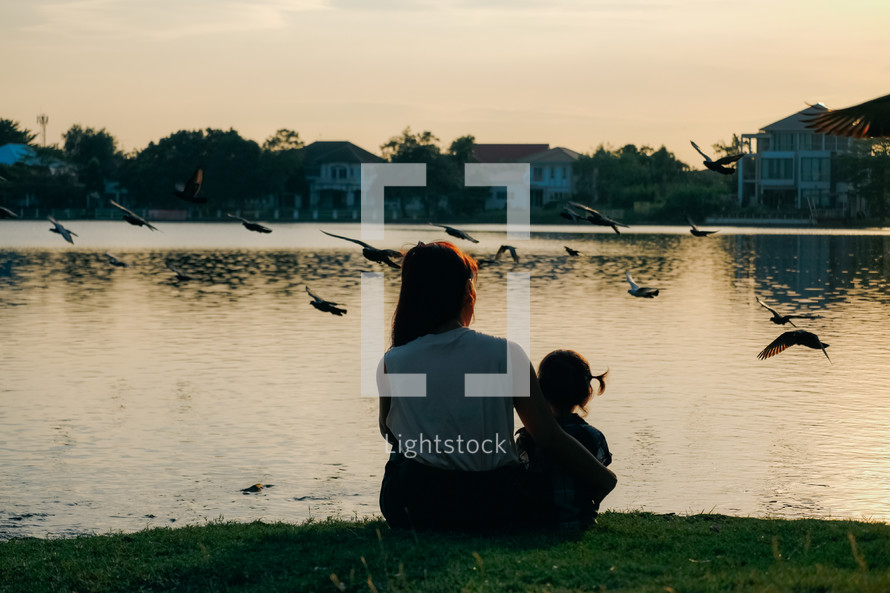 mother and daughter sitting by a pond at sunset