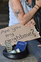 homeless woman begging for money holding a sign - are you my neighbor?