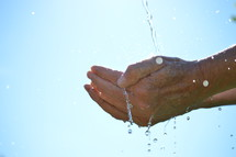 water flowing from the sky into open cupped hands