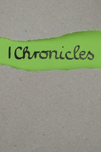 torn open kraft paper over green paper with the name of the 1 book of Chronicles