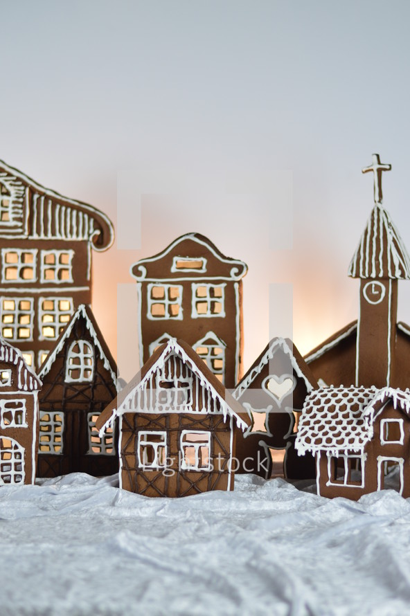 home made gingerbread village with church in front of white background on white snowlike velvet as advent decoration