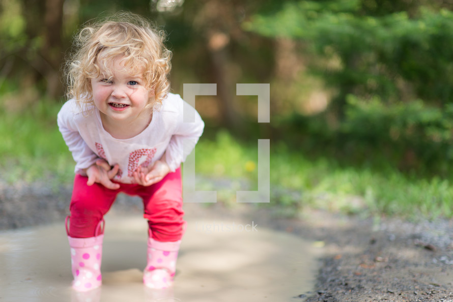 toddler girl playing in a puddle