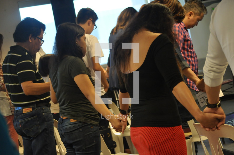 holding hands in prayer during a worship service