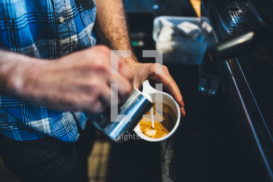 man pouring creamer in coffee