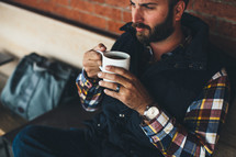 man sitting holding a cup of coffee