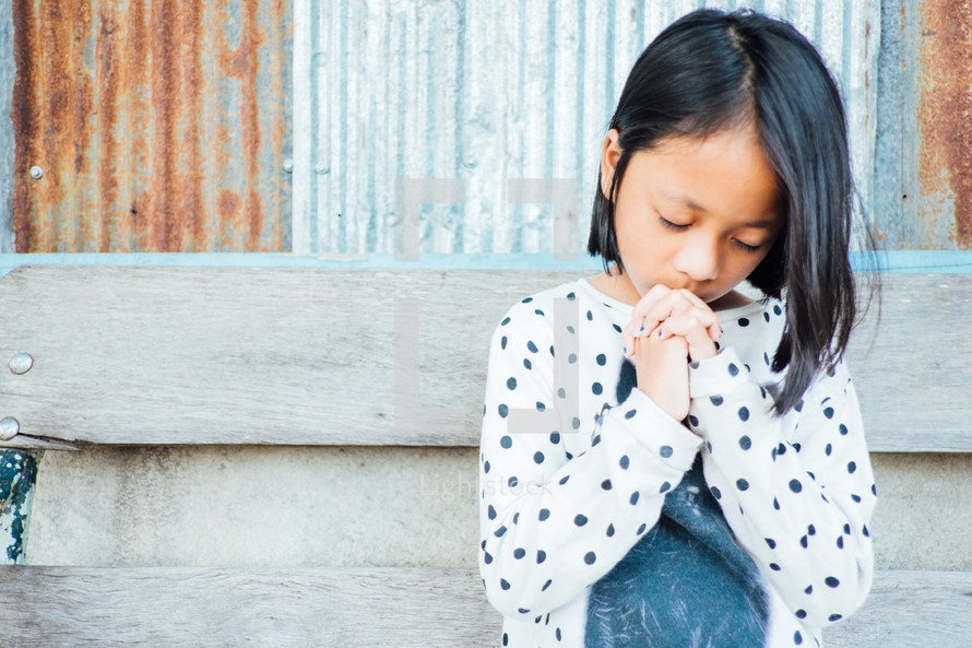praying little girl in front of rusty sheet metal