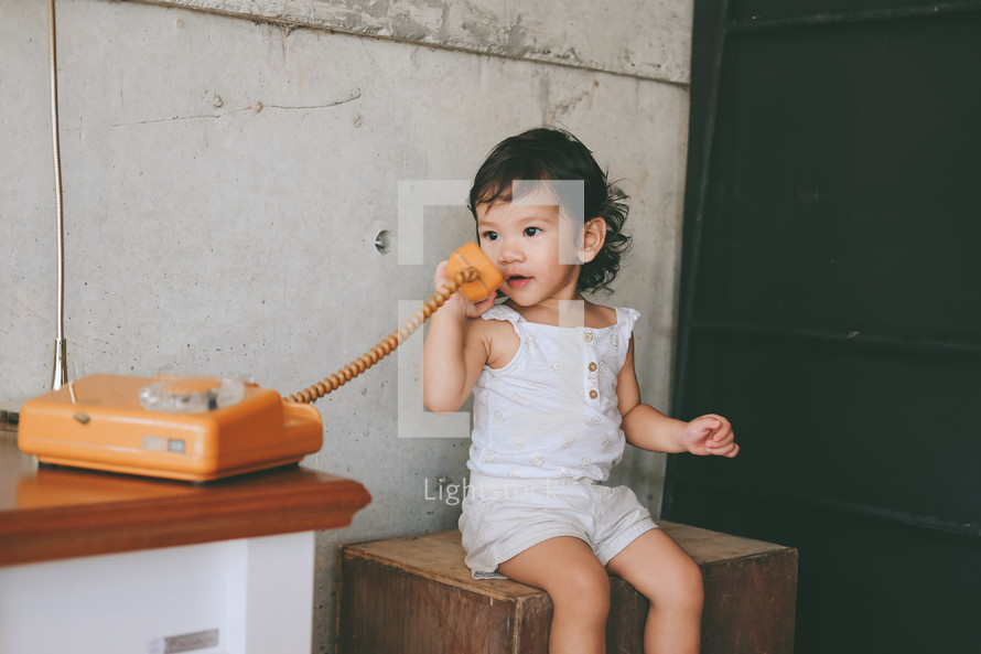 toddler girl talking on a vintage telephone