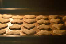 pricked out heart shaped cookies baking in the oven