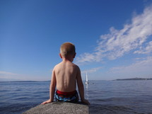 boy watching sailboats