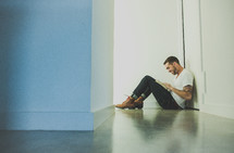 A man sitting in a hallway reading a Bible