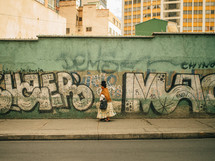 A Latin American woman walks along a graffiti covered wall.
