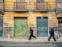 Two men walking along a street of colorful buildings and graffiti.