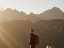 man standing on a mountain with sunlight shining on him