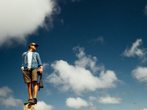 A man balances on top of a rock, with the sky behind him.