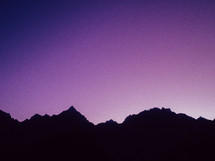 silhouette of mountains and a purple sky