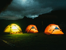 Tents glowing with light on a mountaintop.