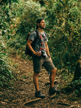 man with a camera standing in a jungle