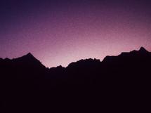 A purple sky illuminates a silhouette of mountains at dusk.