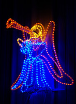 A Christmas Angel blows a trumpet announcing the birth of Jesus made out of neon blue and orange rope lights lighting up the night sky at Christmas with a blue and orange glow.