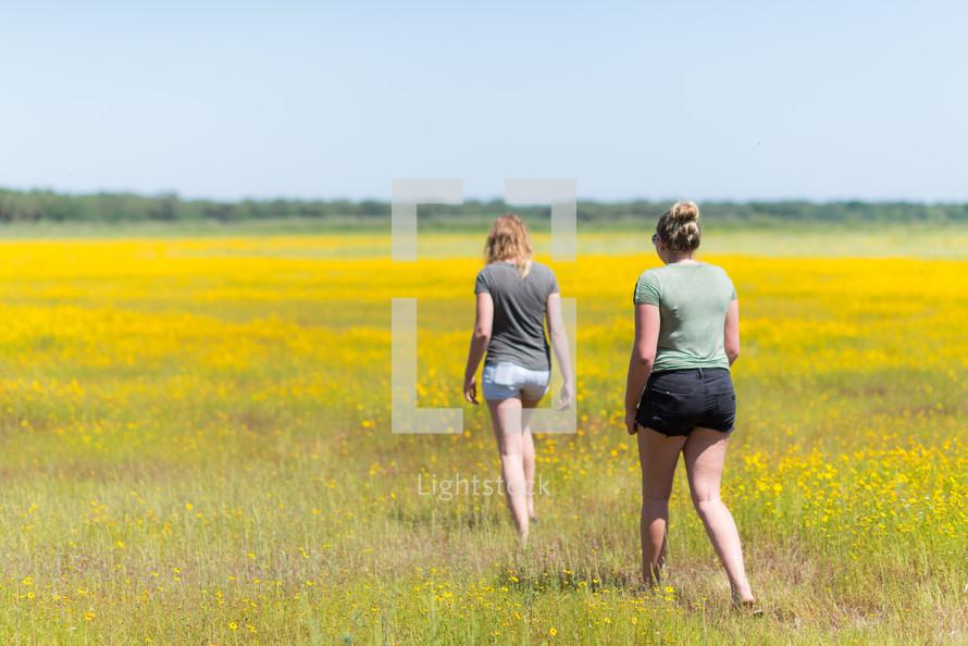 teen girls walking through a field of yellow flowers