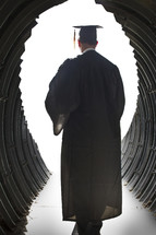 man walking through a tunnel in his cap and gown on graduation day