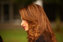 side profile of a woman with red hair and red lips