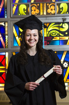 graduate holdin her diploma in front of a stained glass window