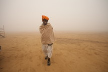 man walking in a desert during a dust storm