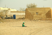toddler sitting in sand in front of a stone hut