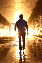 man walking through a glowing wet tunnel