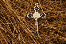 silver crucifix necklace on straw