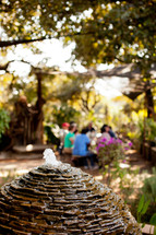 Water fountain and people gathered at a table in Malawi, Africa.
