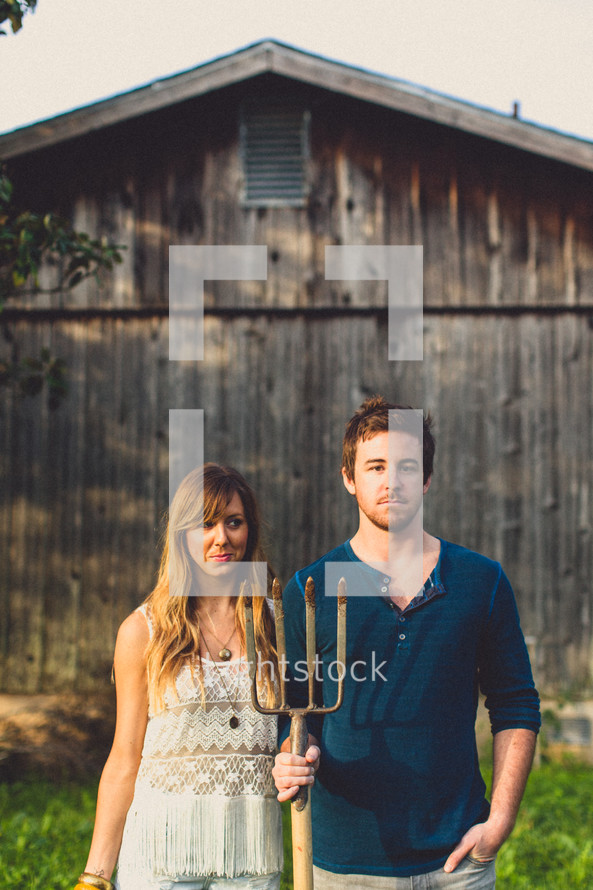 man and woman holding a pitchfork