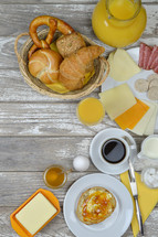 breakfast table with lots of fresh food like coffee, rolls, cheese, sausages, eggs, orange juice, jam, butter and a basket full of croissant, rolls and pretzel with copy space to the left