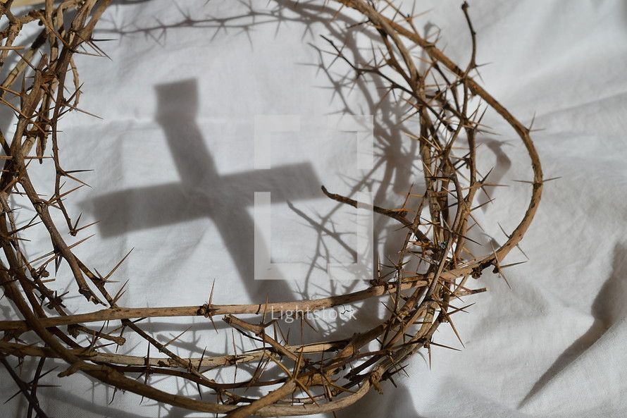 crown of thorns on white cloth and cross shadow