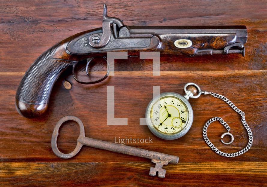 vintage gun, pocket watch, and skeleton key