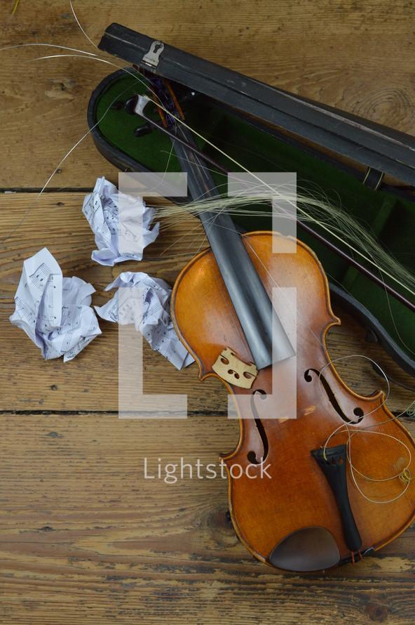 old broken violin on rural wooden floor with antique violin case and tattered fiddlestick