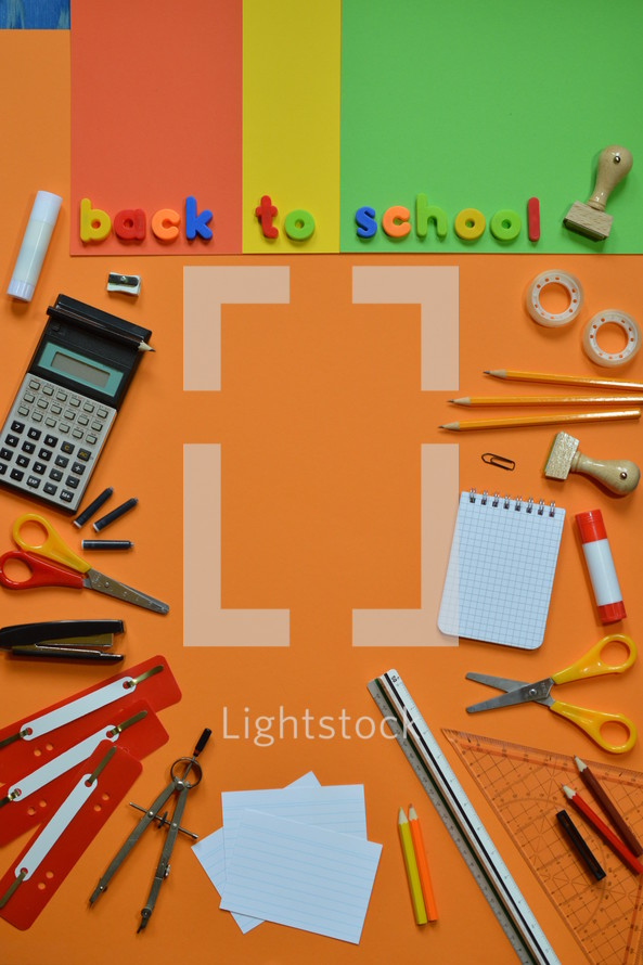 School supplies on colorful paperboard and the words BACK TO SCHOOL