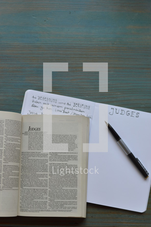 bible studies with a bible open at the book of Judges with notes and pen on a wooden cyan desk